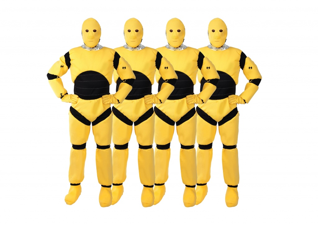 Four men wearing yellow crash test dummy costumes.