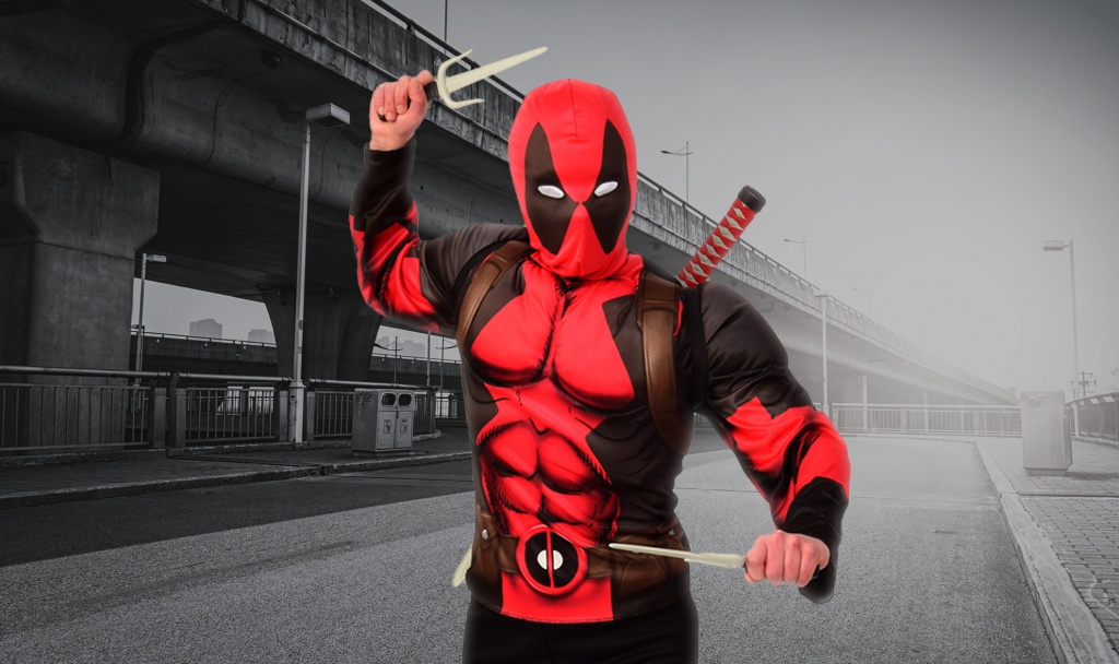 Person dressed in a red and black Deadpool costume with weapons.