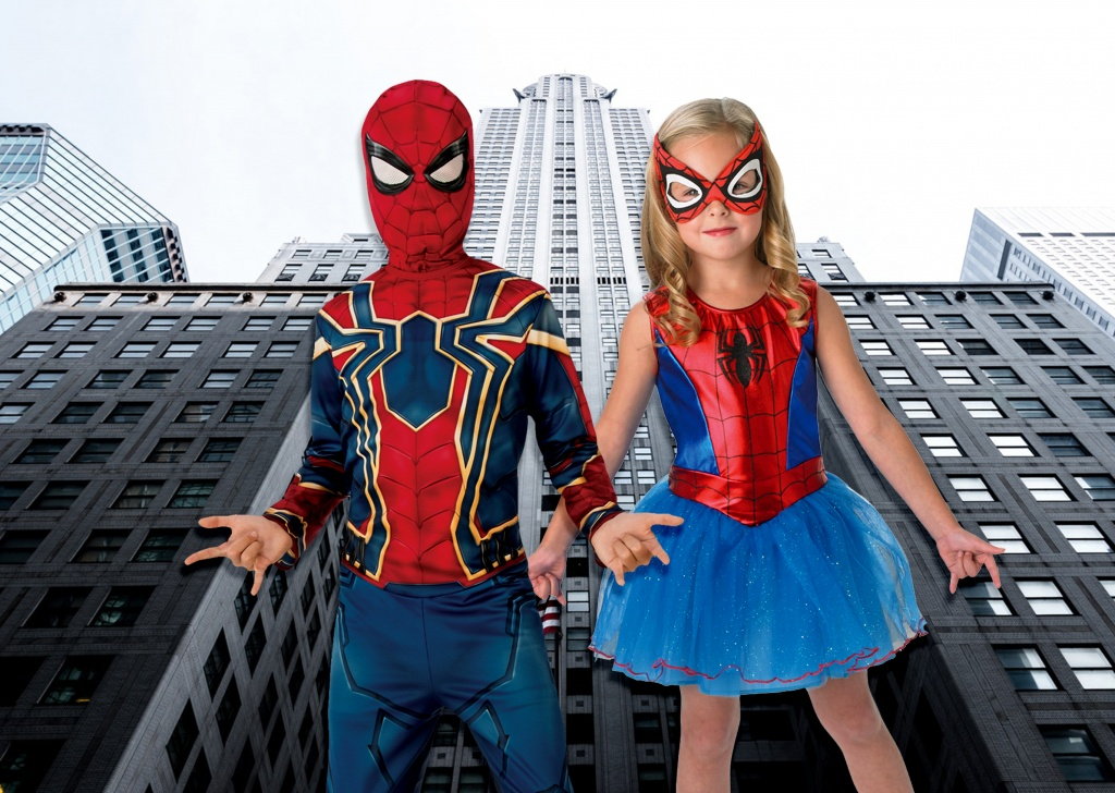 Boy and girl dressed in Spiderman costumes in front of high rise buildings.
