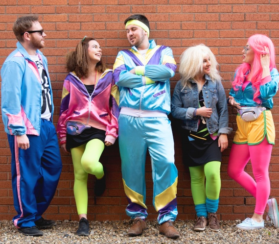 A group of people wearing 80s fancy dress.