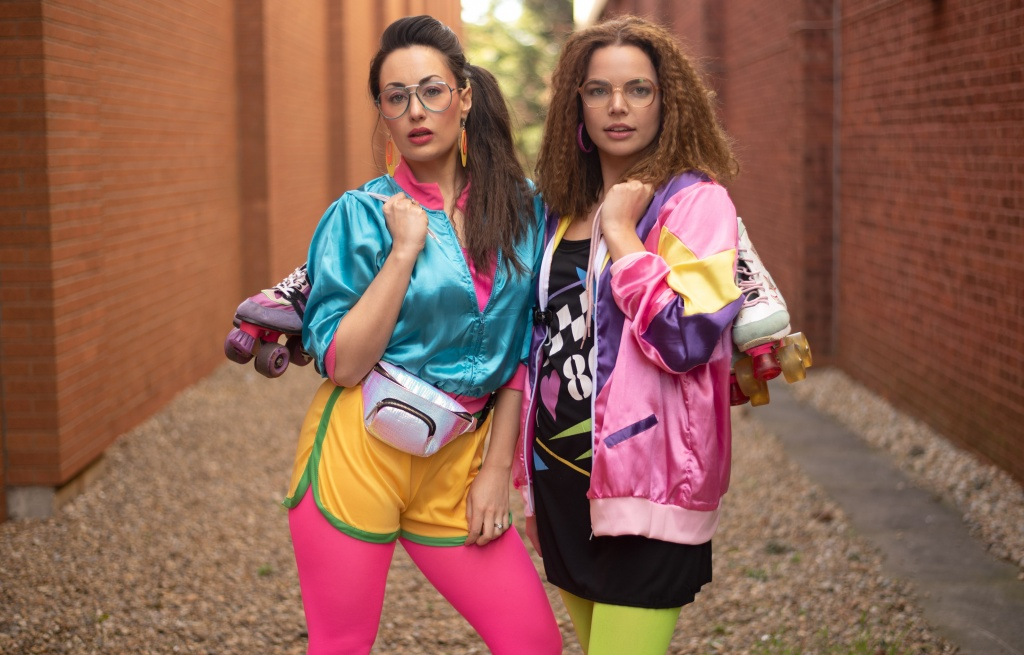Two girls wearing shellsuits with roller skates.