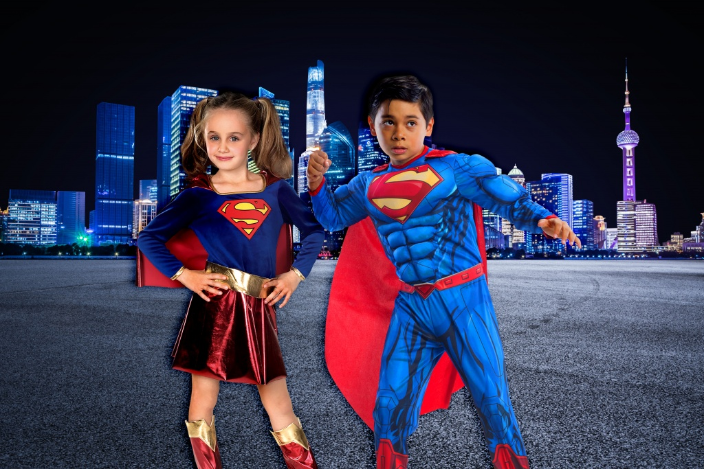 Boys and Girls Superman costumes in front of city scene.